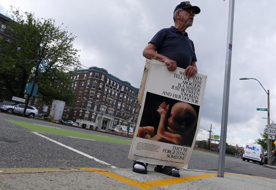 Ray Neary stood behind the yellow line as he protested outside of a Planned Parenthood on Commonwealth Avenue in Boston.